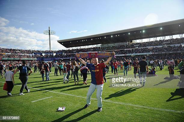 An FC Barcelona fans celebrates his team's 24th La Liga title on the pitch at the end of the Spanish league football match Granada CF vs FC Barcelona...