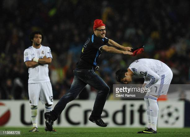 An FC Barcelona supporter throws a traditional catalan hat 'barretina' to Cristiano Ronaldo of Real Madrid during the UEFA Champions League Semi...