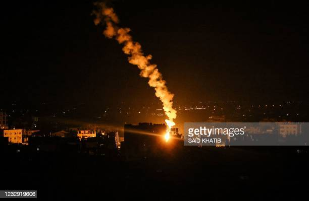 An flare fired by Israeli forces lights the sky above the town of Rafah, in the southern Gaza Strip early on May 16, 2021. - Israeli forces pummeled...