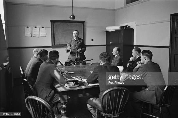 An Flight Sergeant giving weapons instruction to officers sat around a table in a classroom at the RAF Training School at RAF Manby near the village...