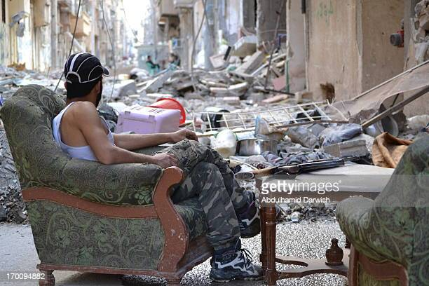 An FSA fighter in Dayr Az Zawr city east of Syria , setting for rest , in one of the most dangerous frontlines of war in the city.