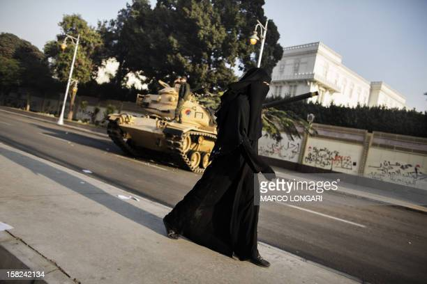 An fullyveiled Egyptian woman walks past an army tank parked outside the presidential palace in Cairo on December 12 2012 Egypt's powerful army has...
