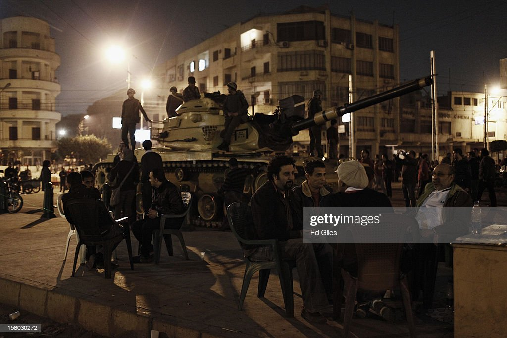 An group of Egyptian protesters drink tea by an Egyptian Republican Guard tank parked by the outer walls of Egypt's Presidential Palace during a demonstration against Egyptian President Mohammed Morsi on December 9, 2012 in Cairo, Egypt. Anti-Morsi protesters continue to demonstrate across Egypt against the country's draft constitution, rushed through parliament in an overnight session on November 29. The country's new draft constitution, passed by a constitutional assembly dominated by Islamists, will go to a referendum on December 15. (Photo by Ed Giles/Getty Images).