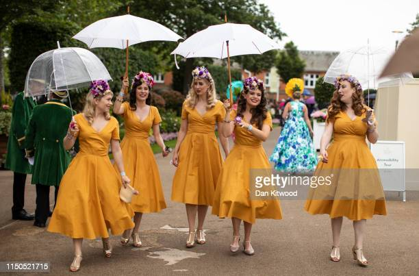 An group of women carry umbrellas as they walk in the rain as racegoers arrive for the first day of races at Ascot Racecourse on June 18, 2019 in...