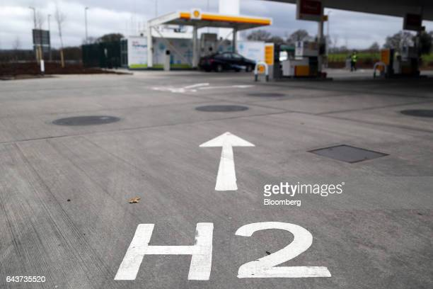 An H2 sign painted on the forecourt directs vehicles towards Royal Dutch Shell Plc's hydrogen refueling pumps at their first UK hydrogen refueling...