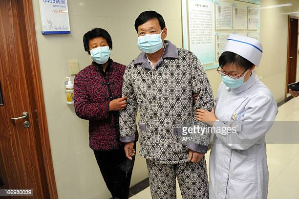 An H7N9 bird flu patient surnamed Li is escorted after his recovery and approval for discharge from the hospital in Bozhou central China's Anhui...