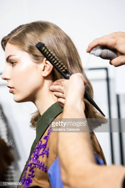 An Hairstylist, hair detail, does the final touch during the line up before the show is seen backstage at the Shi.Rt fashion show during the Milan...
