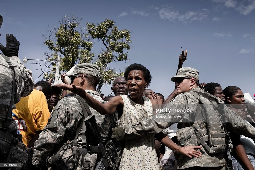 An Haitian elderly woman is hold back by US Soldiers of the 82nd Airborne Division at a food distribution on January 31, 2010 in Port Au Prince, Haiti. As many as 200,000 people died on January 12 as a consequence of the 7.0-magnitude earthquake. At least 130 people have been pulled alive from the rubble. An estimated 1.5 million people have been left homeless. The Haitian government is planning to relocate some 400,000 people, currently in makeshift camps across the capital, to temporary tent villages outside the city. Aid agencies are still struggling to supply food and water to survivors, while thousands of Haitians who suffered serious injuries remain in need of urgent medical attention.