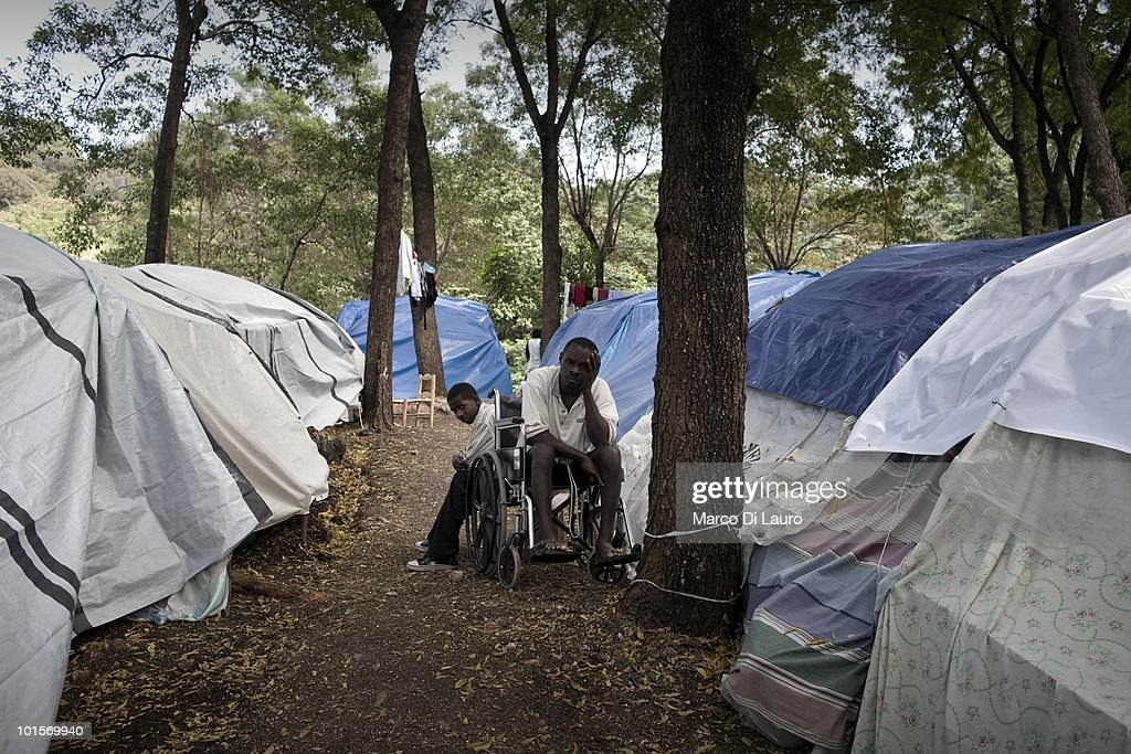 An haitian man on a whealchair and his child are seen in a temporary camp in the Juvena Park on January 30, 2010 in Port Au Prince, Haiti. As many as 200,000 people died on January 12 as a consequence of the 7.0-magnitude earthquake. At least 130 people have been pulled alive from the rubble. An estimated 1.5 million people have been left homeless. The Haitian government is planning to relocate some 400,000 people, currently in makeshift camps across the capital, to temporary tent villages outside the city. Aid agencies are still struggling to supply food and water to survivors, while thousands of Haitians who suffered serious injuries remain in need of urgent medical attention.