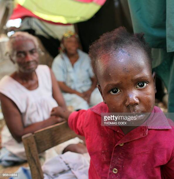An Haitian young girl reacts under a tent with her familly where they took refuge in the middle of destroyed houses' rubbles in downtown Leogane 17...