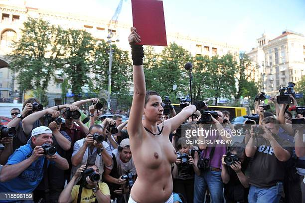 An half naked activist and protestor from the Ukrainian women's right movement FEMEN whistles and waves a file with a sign reading 'EURO2012 without...