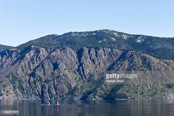 An happy adventurous retired couple kayaking on a huge calm lake in Idaho.