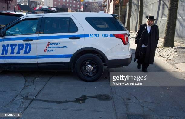 An Hasidic man walks past a patrol car on December 12 2019 in the Williamsburg neighborhood of Brooklyn New York