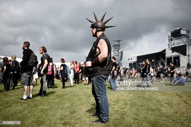 An Heavy metal fan wearing a helmet attends the Hellfest heavy metal and hard rock music festival on June 17 2016 in Clisson western France / AFP /...