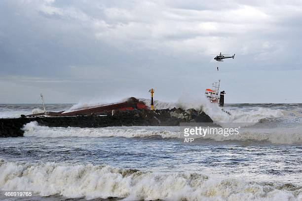 An helicopter airlifts a crew member over a Spanish cargo ship ''Luno'' which slammed into a breakwater and split in two injuring at least one sailor...