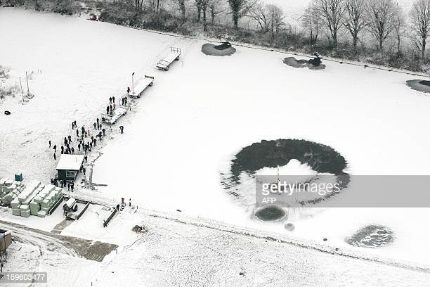 An helicopter flies low above the Veluwemeer a lake in central Holland on January 17 2013 The helicopter is hired by skatingclubs situated along the...