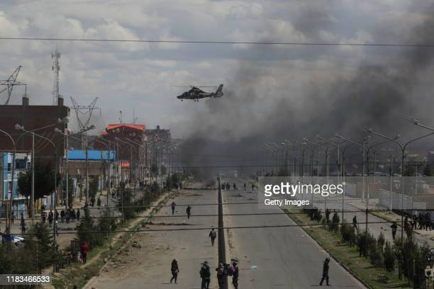 An helicopter flies next to a road blocked by supporters of Evo Morales Ayma as clashing with police during protests on November 19, 2019 in El Alto,...