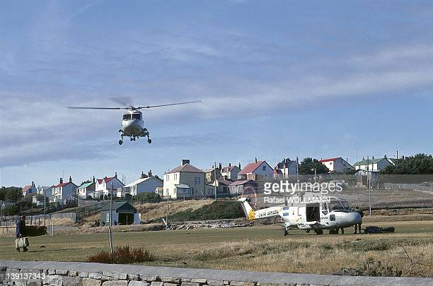 An helicopter flys in with another one on the ground with British soldiers surrendered to Argentine troops that invaded the islands on April 2, 1982...