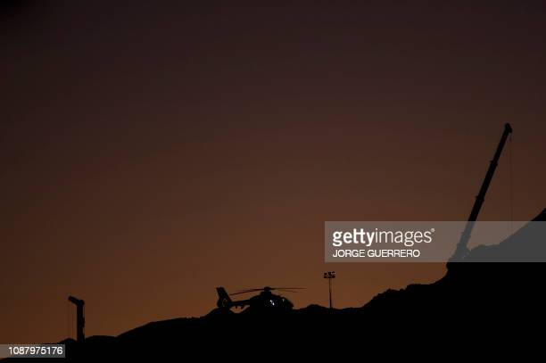 An helicopter of the Spanish Guardia is pictured next to a crane at the site where a child fell down a well in Totalan southern Spain on January 24...