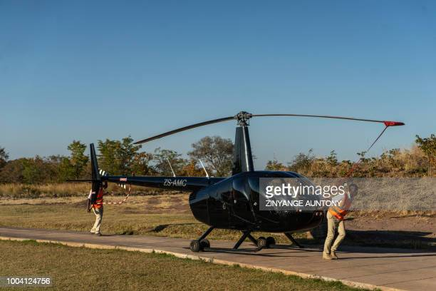 An helicopter used for tourism is pushed into a parking bay on June 28 2018 in the resort town of Victoria Falls After nearly two decades in the...