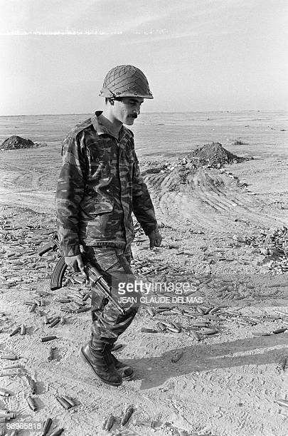 An helmeted kalachnikov armed Iraqi soldier walks among cartridges in the area of the alHoweizah marshes Southern Irak 20 March 1985 after his unit...