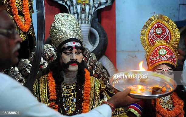 An Hindu devotee performs 'Arti' as he offers prayers to an artist dressed as demon king Ravana ahead of a religious procession Ravan ki Barat in...