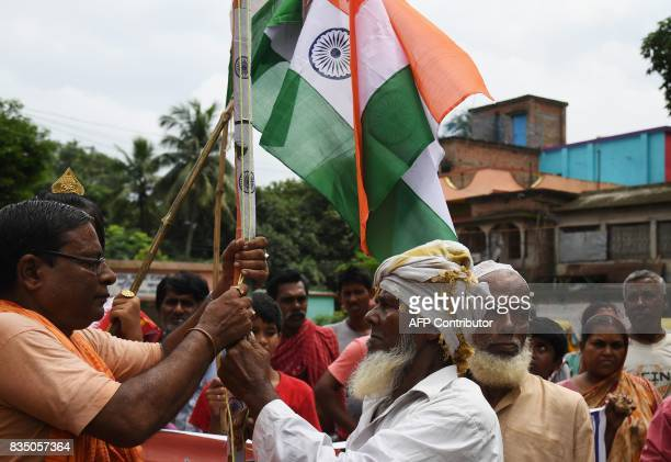 An Hindu priest and Muslim mawlawi hoist the Indian national flag to celebrate Indian Independence Day in Majhdia village of Nadia district east of...