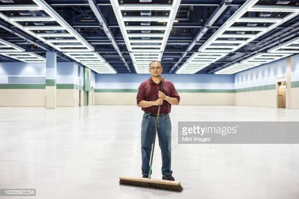 an hispanic man standing with a broom in a large convention center space. - janitor stock photos and pictures