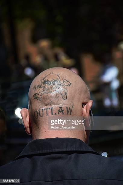 An Hispanic man with a skullandcrossbones tattoo on his head watches a lowrider custom car parade through Santa Fe New Mexico on May 22 2016