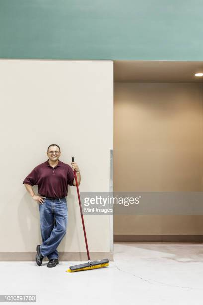 an hispanic workman standing in a large interior space with a broom. - janitor stock photos and pictures