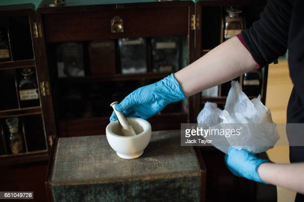 An Historic Royal Palaces preventive conservator removes a pestle and mortar from a Georgian medicine cabinet in the 'Queen's Bedroom' in Kew Palace...