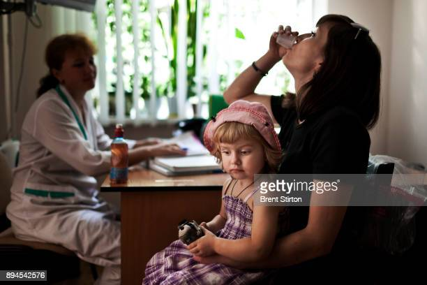 An HIV mother swallows her Methadone dosage at a drug substitution program using Methadone to substitute for Heroin at the Kiev Aids Center in Kiev...