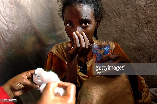 An HIV positive Ethiopian girl gets 27 May 2005 her free antiretroviral that she periodically receives for her treatment in Makaniza one of the...