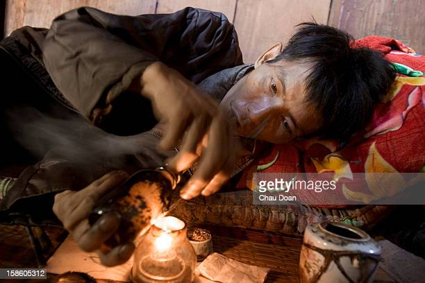 An H'mong ethnic opium addict smokes opium at his house in Hong Ngai district Son La province Son La Province situated between China and Laos is a...