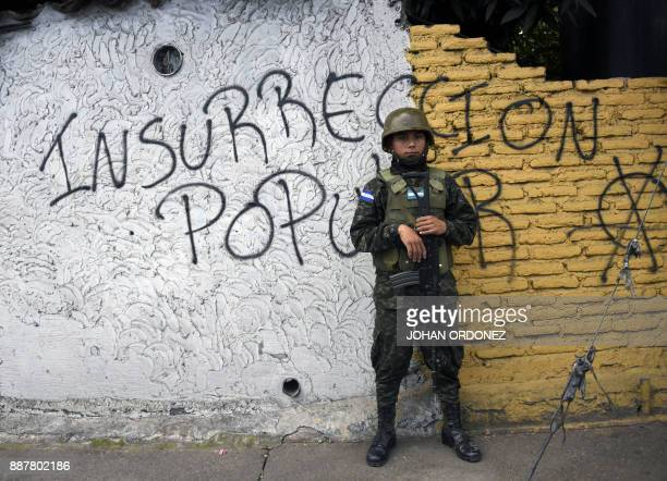 TOPSHOT An Honduran Army soldier stands guard in front of a graffiti reading Popular insurrection as supporters of Honduran President and...