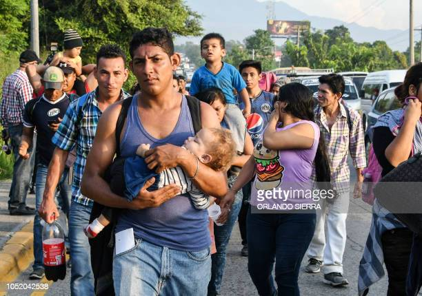An Honduran man carries a child on is arms during an exodus towards the US from San Pedro Sula 180 kms north from Tegucigalpa on October 13 2018...