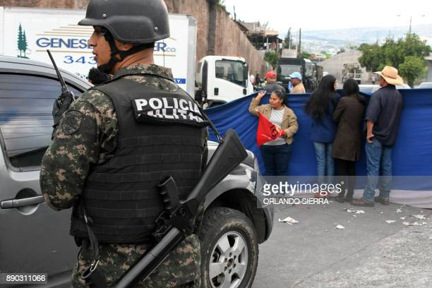 An Honduran policeman stands guard as supporters of presidential candidate for Honduras' Opposition Alliance against Dictatorship Salvador Nasralla...
