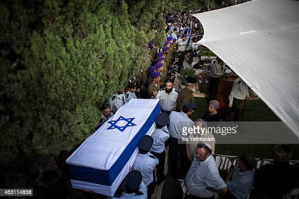 An honor guard caries the coffin of Israeli Lt Hadar Goldin during his funeral on August 3 2014 in Kfarsaba Israel Goldin was thought to have been...