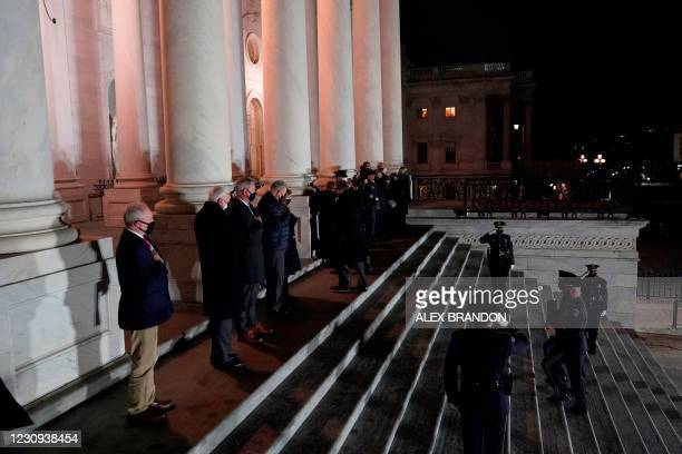 An honor guard carries an urn with the cremated remains of US Capitol Police officer Brian Sicknick and a folded American flag up the steps of the US...