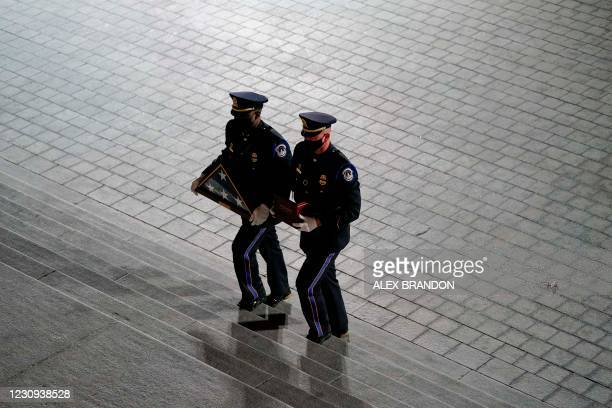An honor guard carries an urn with the cremated remains of US Capitol Police officer Brian Sicknick and a folded US flag up the steps of the US...