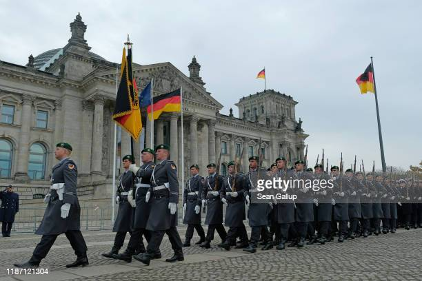 An honor guard marches past the Reichstag following a ceremony in which new recruits of the Bundeswehr the German armed forces took their oath of...
