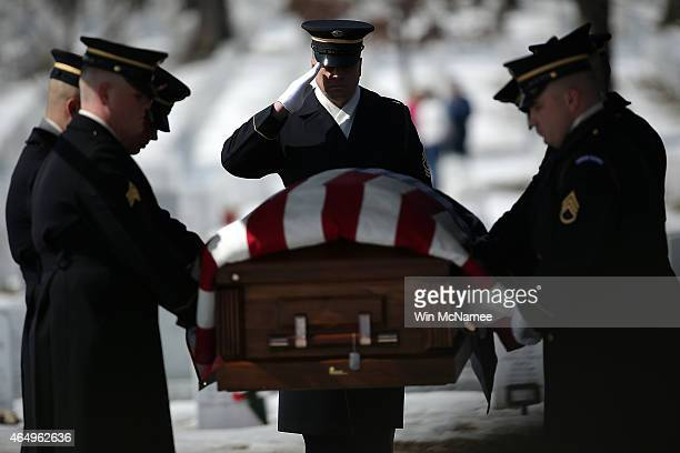 An honor guard moves the remains of US Army Air Forces Tech Sgt Charles Johnston to his burial site at Arlington National Cemetery March 2 2015 in...