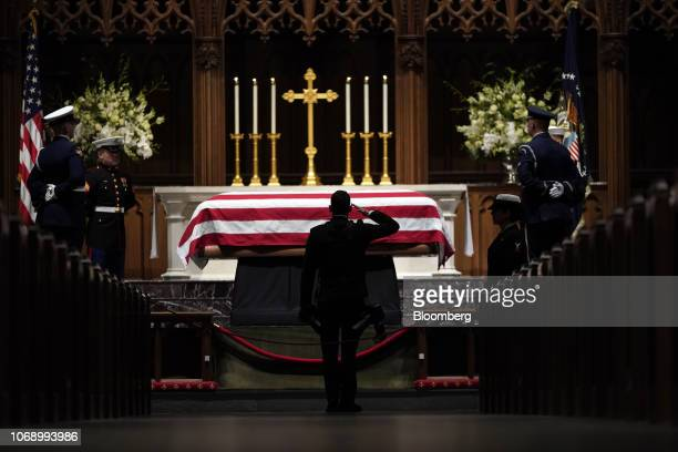 An honor guard salutes the flagdraped casket of former US President George HW Bush during a funeral service at St Martin's Episcopal Church in...