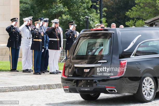 An Honor Guard salutes the hearse carrying the late Sen John McCain RAriz after his funeral at the Washington National Cathedral on September 1 2018