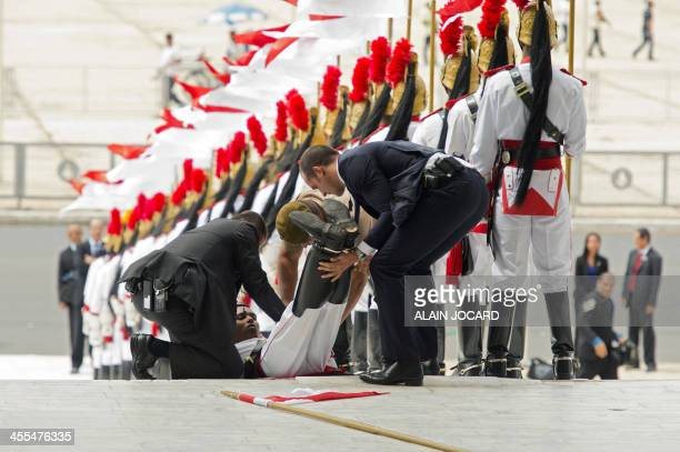 An Honor Guard soldier receives first aid after he fainted due to intense heat before the arrival of French President Francois Hollande at Planalto...