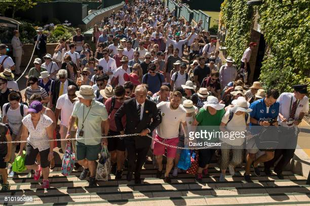 An Honorary Steward guides the crowd towards Murray Mound ahead of day five of the Wimbledon Lawn Tennis Championships at the All England Lawn Tennis...