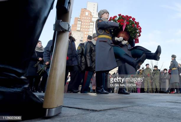 An honour guard brings a flowerpot during a commemorative ceremony for the Soviet victims of the war in Afghanistan in SaintPetersburg on February 15...