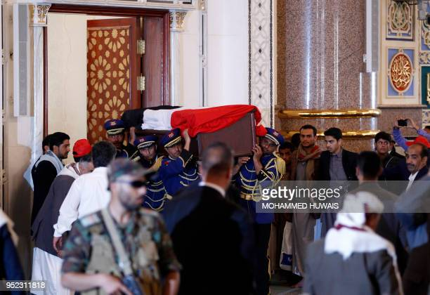 An honour guard carries the coffin of slain Huthi leader Saleh alSamad and his six body guards during his funeral at a mosque in the Yemeni capital...