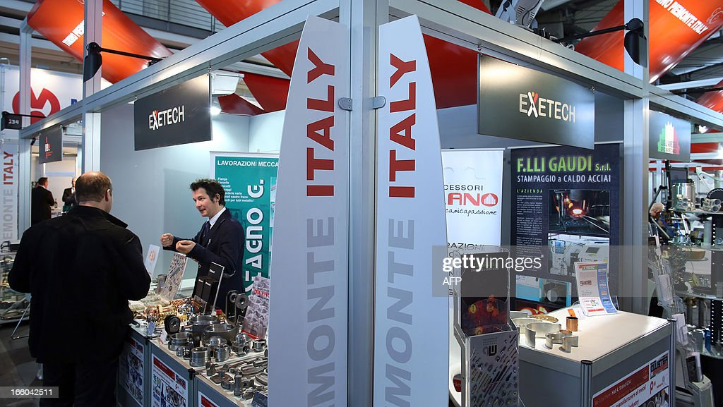 Exhibition Booth In Spanish : An host of exetech chats with a vistor at spanish booth at the