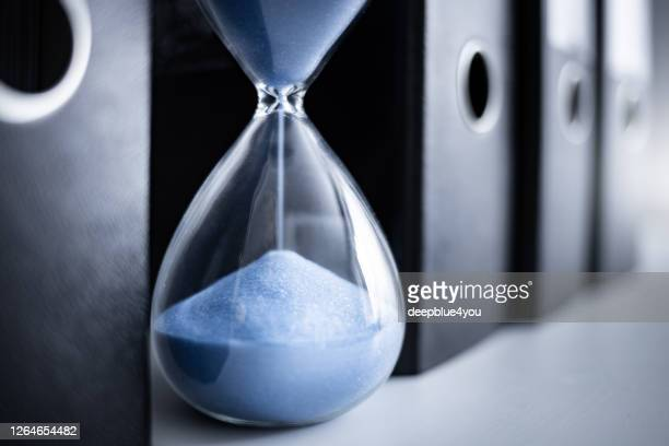 an hourglass runs between file folders - fiscal year stock pictures, royalty-free photos & images